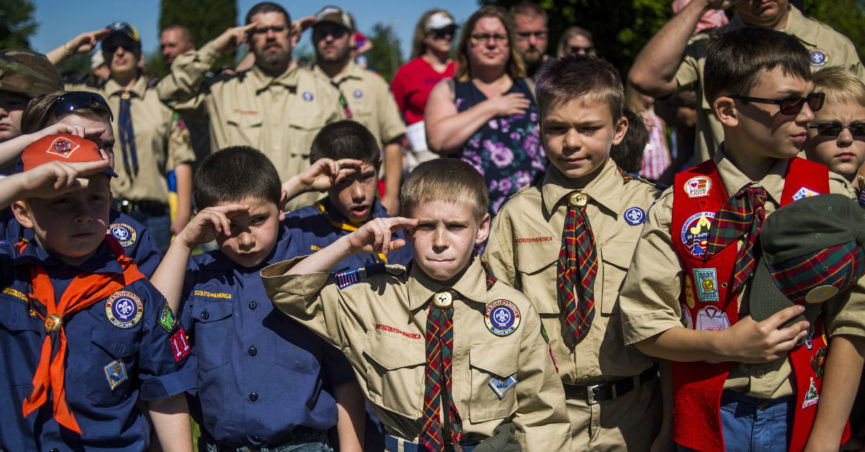 Eli Whalen, 10, center, purses his lip as he salutes the lives of fallen soldiers who have made the ultimate sacrifice dying for their country in battle while paying his respects alongside fellow Boy Scouts and Cub Scouts alike on Memorial Day amidst hundreds of families attending a ceremony on Monday, May 29, 2017 at Fairview Cemetery in Linden, Mich. (Jake May /The Flint Journal-MLive.com via AP)